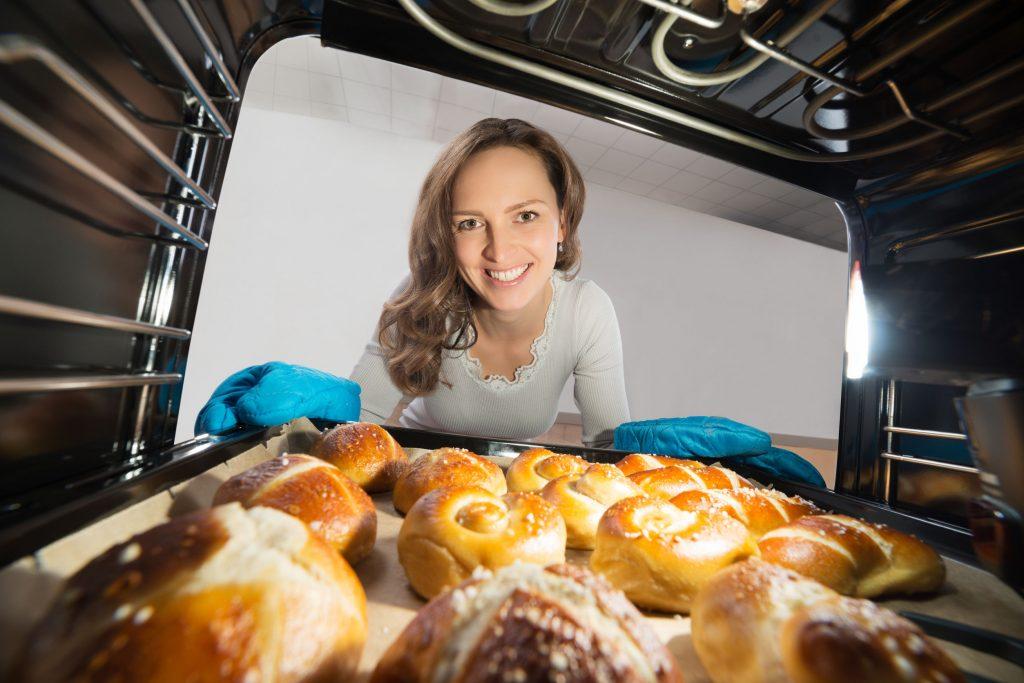 Mujer joven quitando la bandeja de panecillos vista desde el interior del horno microondas