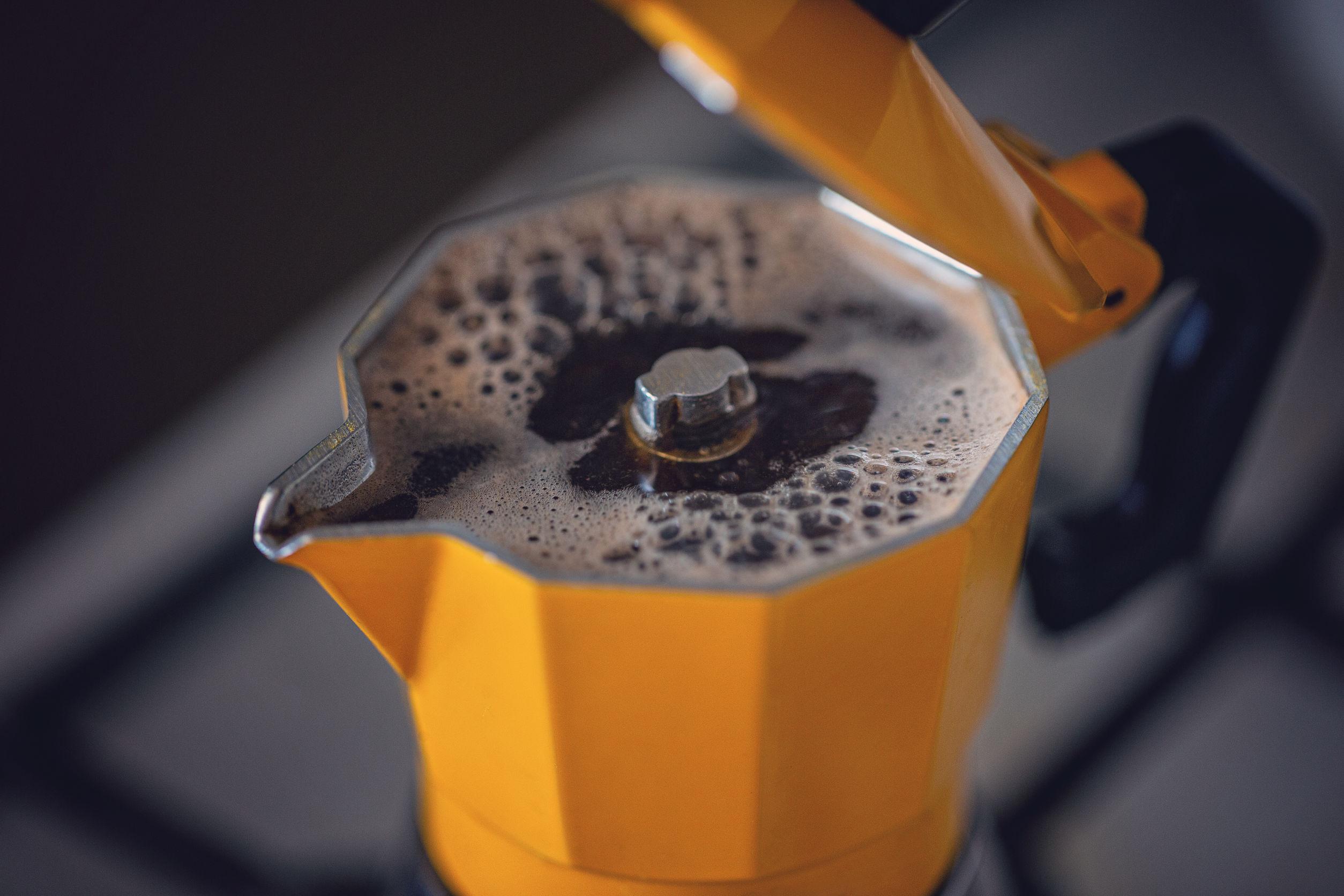 El proceso de preparación de café en un punto de cafetera sobre un fondo oscuro.