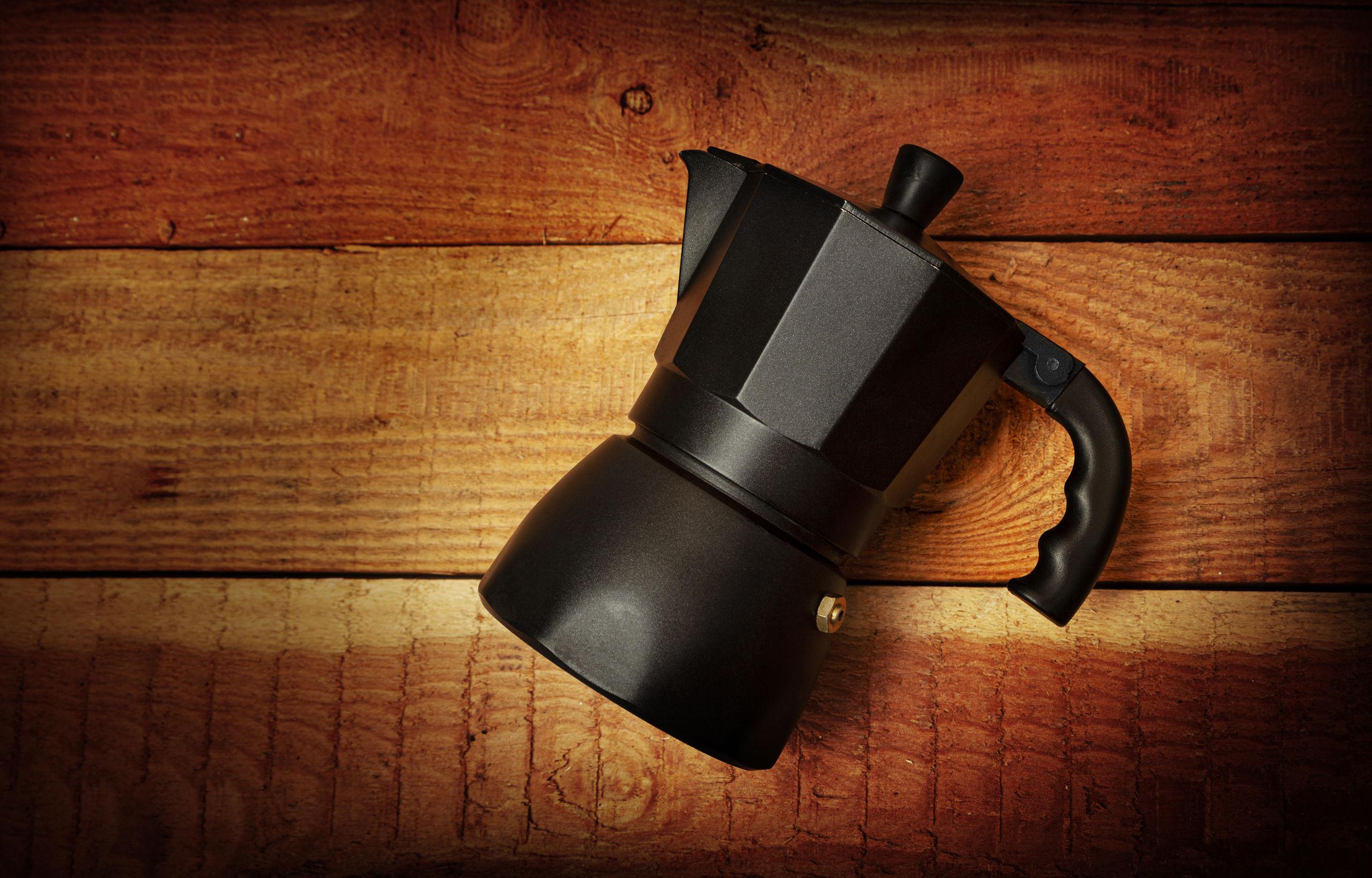 cafetera italiana negro aislado sobre fondo de madera