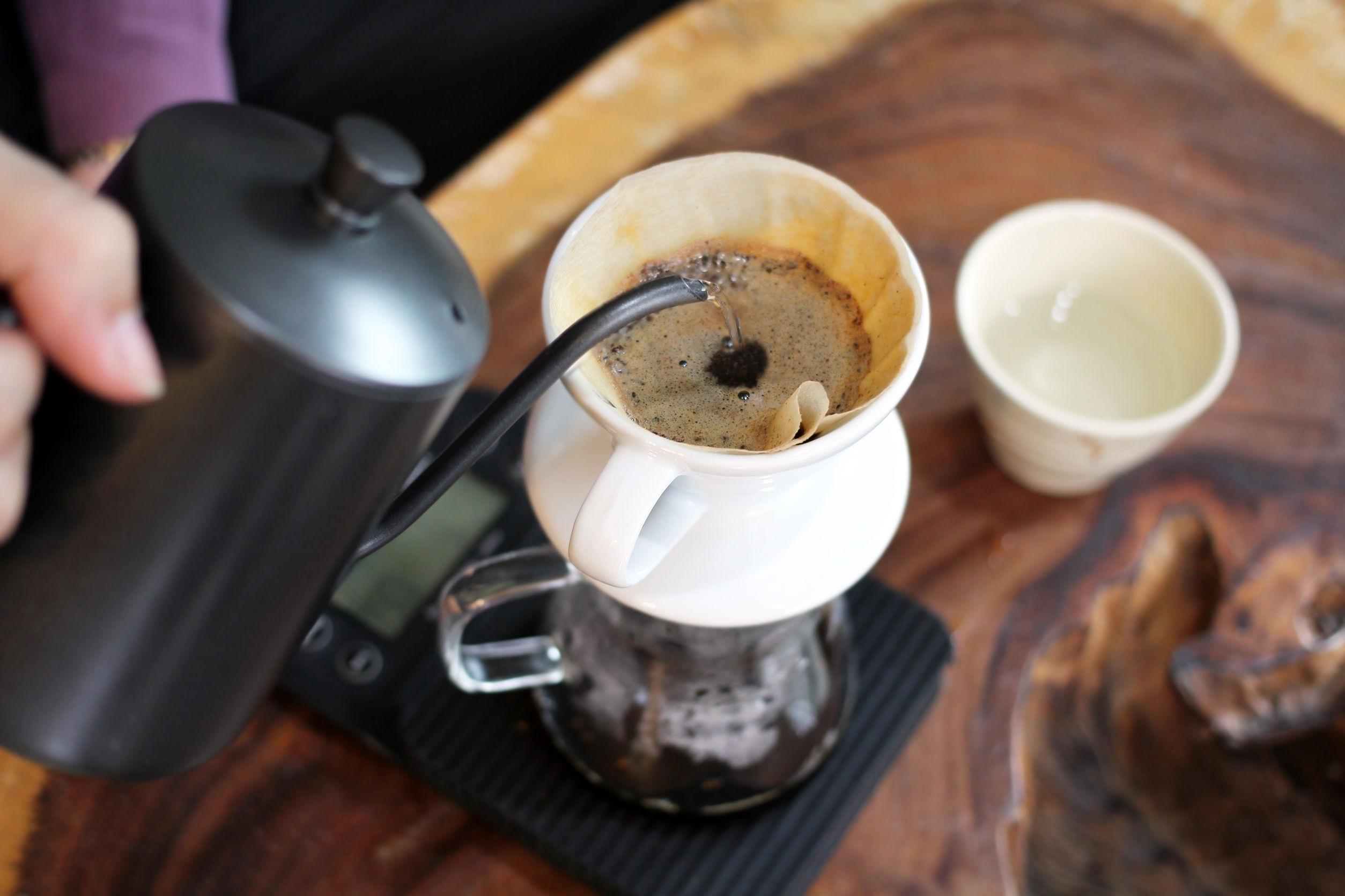 Barista vertiendo agua caliente sobre polvo de café molido tostado