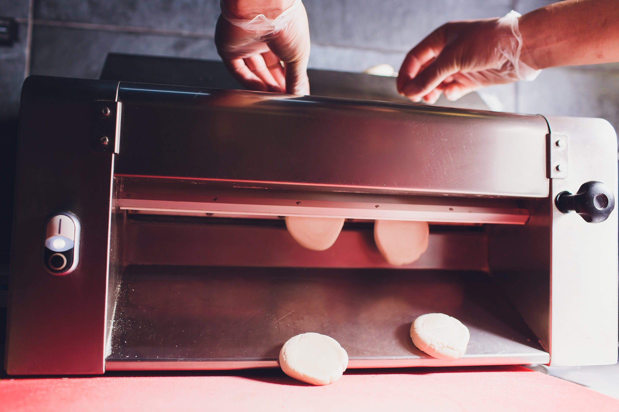 Persona haciendo bollos en laminadora de masa